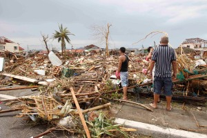 Survivors assess the damage after super Typhoon Haiyan battered Tacloban city, central Philippines